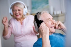 Happy senior couple in headphones having fun together at home